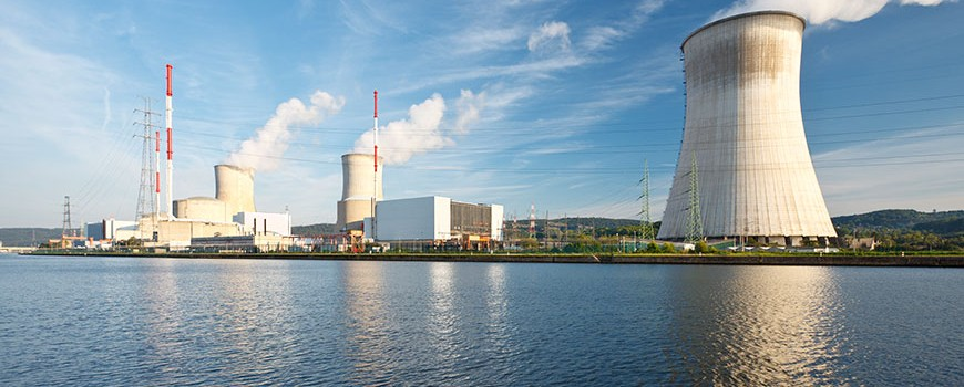 Nuclear power plant at a river with blue sky and some clouds